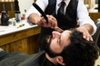 Crop barber using razor to shave beard of young man sitting in chair.