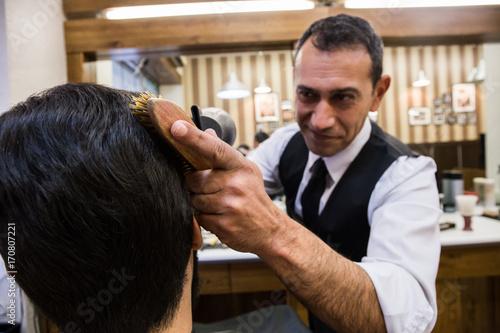 Smiling adult man working in barbershop setting hair of customer using hairdryer.