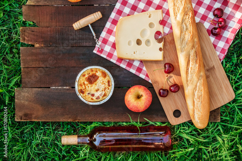 Keuken foto achterwand Picknick Picnic food and rose wine on green grass with copyspace