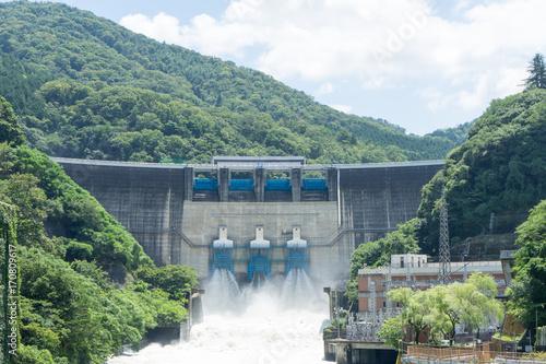 Deurstickers Dam 台風通過後に放流する天ヶ瀬ダムの景色