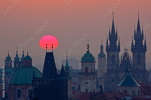 Staande foto Praag Twilight in historical city. Magical picture of tower with orange sun in Prague, Czech Republic, Europe. Beautiful detailed sunrise view of Prague church towers. Early morning colours with old town.