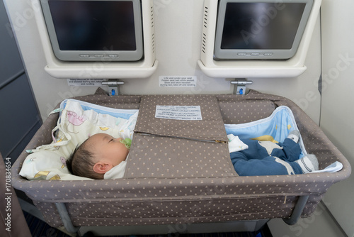 Photo Asian adorable baby boy sleeping In special bassinet on airplane.
