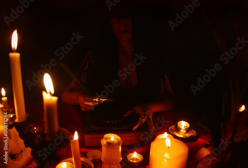 A witch carrying out a ritual with magic book and candles  Halloween