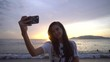 Woman take selfie on smartphone in front of sunrise over the ocean