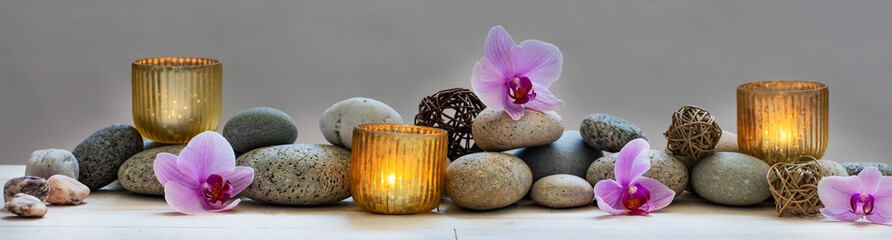 Fototapeta na wymiar concept of wellbeing with pebbles, orchids and candles, panoramic