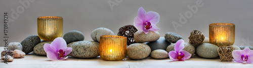 Foto op Aluminium Spa concept of wellbeing with pebbles, orchids and candles, panoramic
