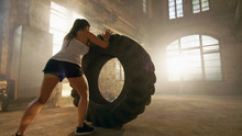 Fit Athletic Woman Lifts Tire As Part Of Her Cross Fitness/ Bodybuilding Training.