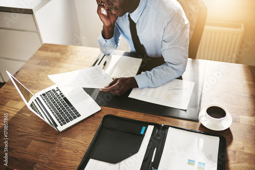 Photo  Young businessman working online and reading paperwork over the