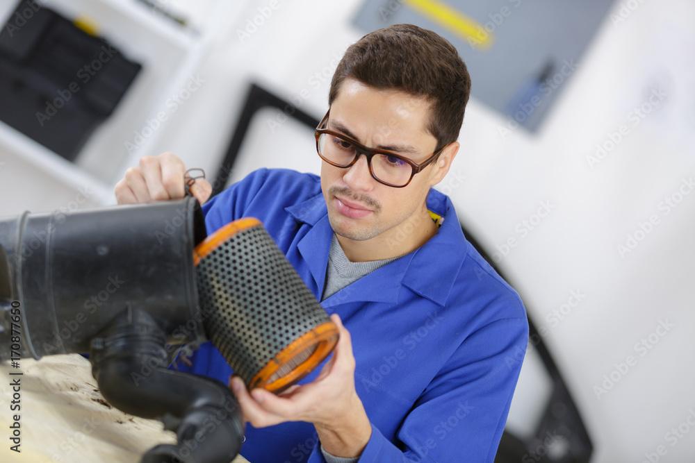 Fototapeta professional mechanic cleaning filter in his workshop