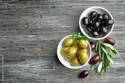 Bowls with tasty olives on wooden background