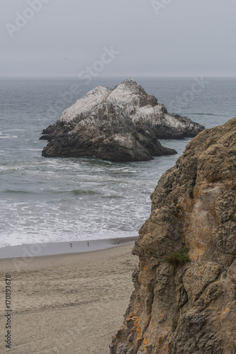 Cliff in the foreground, sandy beach below, with ocean water