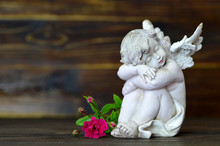 Sleeping Angel And Single Rose On Wooden Background