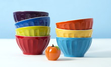 Colorful Ceramic Bowls With Glass Apricot On Blue Background