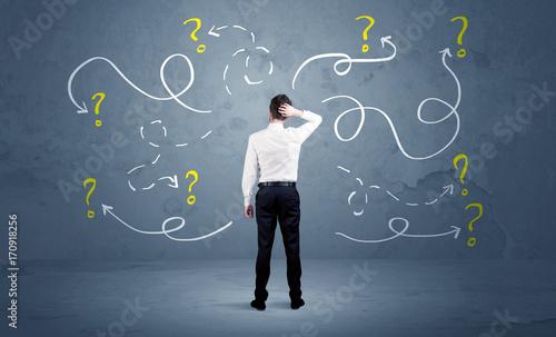 Fotografía Unsure businessman with question marks