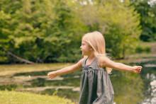 Portrait Of Happy Little Girl In Dress In Summer