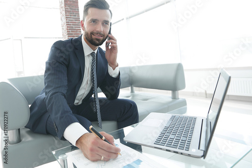 Garden Poster Businessman talking on smartphone about financial charts.