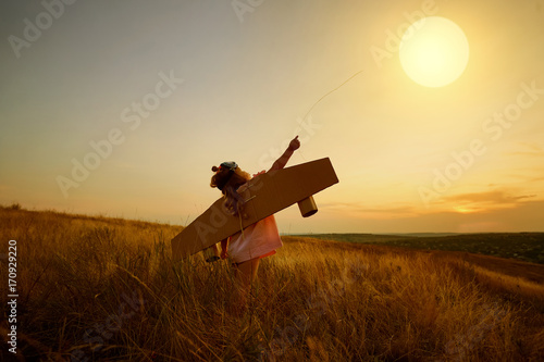 Fotografia  Little girl in pilot's suit in field on nature at sunset.