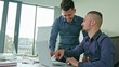 Two Man in modern start up office male team leader pointing at screen discussing diverse people group teamwork using laptop display