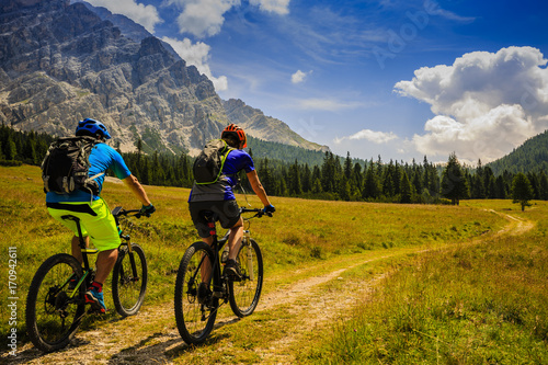 Aluminium Prints Cycling Mountain cycling couple with bikes on track, Cortina d'Ampezzo, Dolomites, Italy
