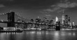 Time-lapse of Lower Manhattan Financial District skyscrapers, Brooklyn Bridge, and East River with passing clouds at twilight in Black & White. Manhattan, New York City