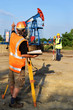 Two engineers - land surveyors at work on an European oil well