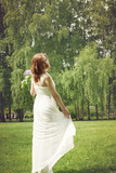 Fototapeta Las - A girl in a white dress stopped walking in the park and looked back, holding the dress. A branch of lilac in the other hand, a summer landscape in the background.