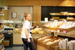 Woman with a smartphone choosing bread from a supermarket