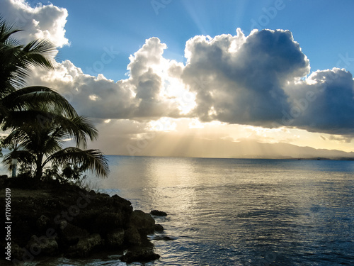 Foto op Plexiglas Caraïben Beautiful sunset over the sea with a view at palms with cloudy sky in Guadeloupe, Caribbean, Antilles.
