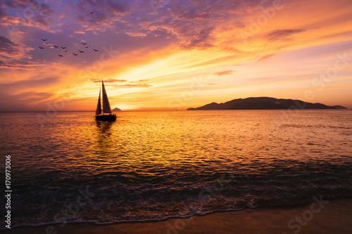 Fotografia Sailboat on the ocean at sunrise