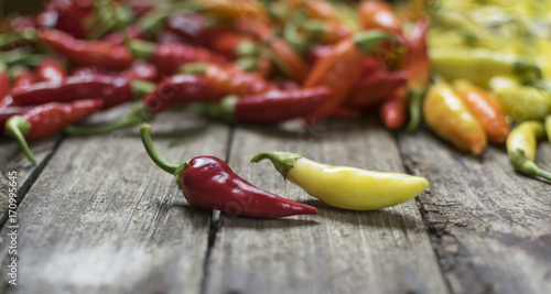 Staande foto Hot chili peppers Two chilli peppers in front of large group of peppers on wooden table . Selective focus