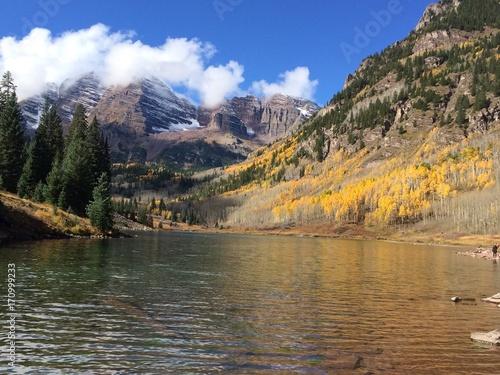 nieduze-gorskie-jezioro-oraz-widok-na-drzewa-i-chmury-ponad-gorami