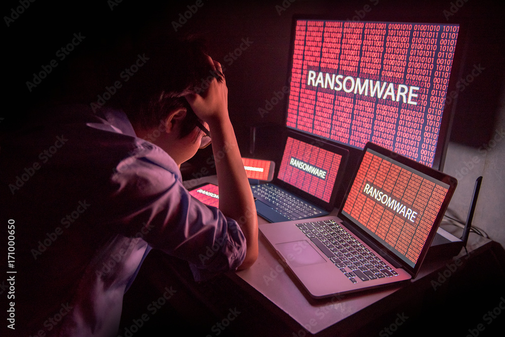 Fototapeta Young Asian male frustrated, confused and headache by ransomware attack on desktop screen, notebook and smartphone, cyber attack and internet security concepts