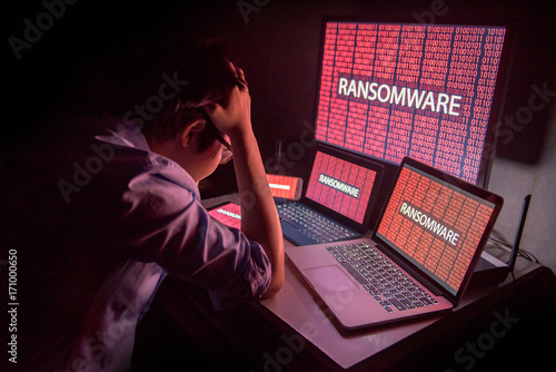 Leinwand Poster Young Asian male frustrated, confused and headache by ransomware attack on deskt