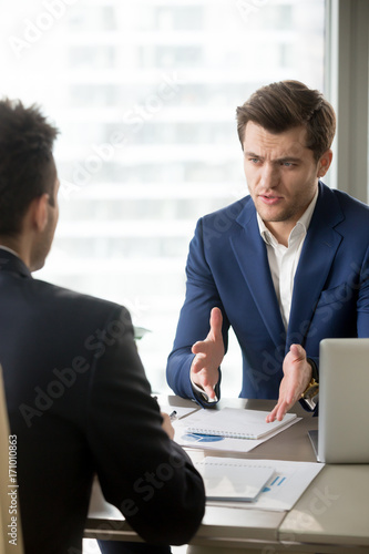 Serious successful businessman discussing company results with financial directo Canvas Print
