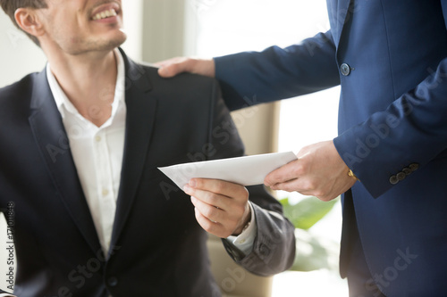 Fototapeta Company leader giving money bonus in paper envelope to happy smiling office worker, congratulating employee with increasing of salary or promotion, thanking for successes in work. Close up concept obraz