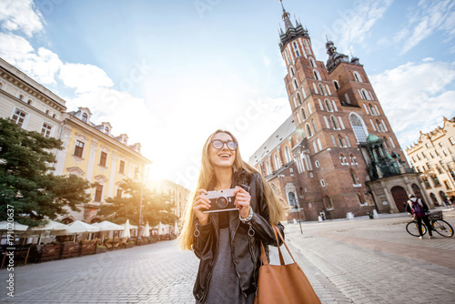 Fototapeta Portrait of a young stylish woman tourist in front of the famous St. Mary's Basilica on the Market square during the sunrise in Krakow, Poland obraz