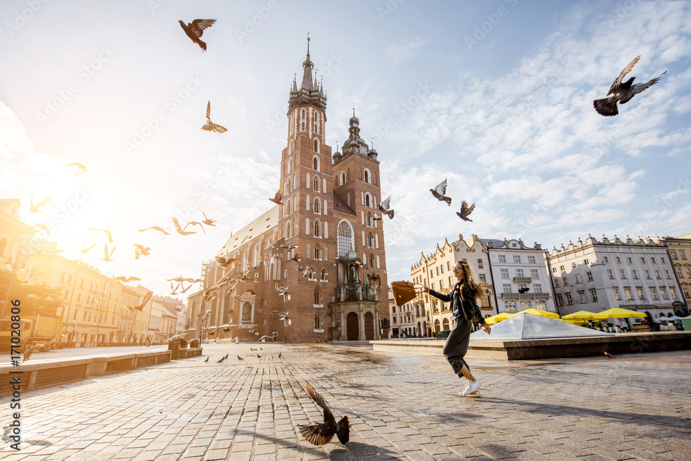 Obraz View on the central square and famous st. Marys basilica with pigeons flying during the sunrise in Krakow, Poland fototapeta, plakat