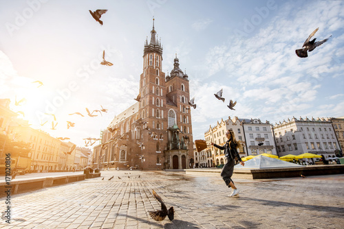 Wall Murals Krakow View on the central square and famous st. Marys basilica with pigeons flying during the sunrise in Krakow, Poland