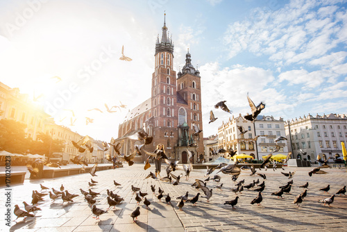 Obraz View on the central square and famous st. Marys basilica with pigeons flying during the sunrise in Krakow, Poland - fototapety do salonu