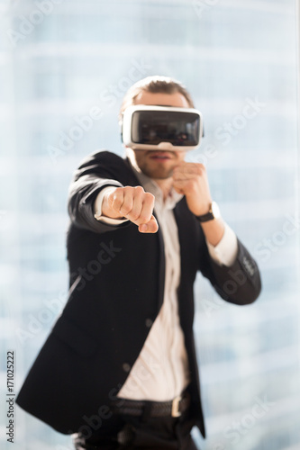 Cuadros en Lienzo Businessman in VR glasses playing boxing game simulator