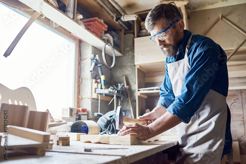 Fotografie, Obraz Bearded middle-aged craftsman wearing safety goggles and apron hammering nails i