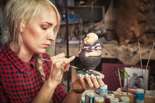 Close-up A Young Blonde Woman In A Checkered Red Shirt Paints A Figurine Of A Small Plump Little Man. From The Fairy Tale Of Alice In Wonderland In The Workshop, On The Table Lie Tools