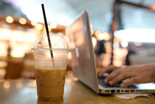 A Half Cup Of Coffee With Soft Light 2 Hands Typing On Laptop. 2 Man Hands Working On Computer In Coffee Shop With A Half Cup Of Ice Coffee On Wooden Table In Airport With Soft Light Bokeh Background