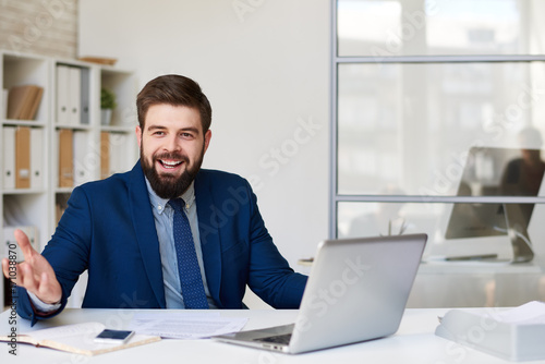 Garden Poster Portrait of successful bearded businessman smiling happily while working at desk i9n modern office