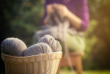 Wicker Basket With Brown Threads Made Of Natural Wool, In The Background A Woman In A Purple Sweater Knits A Sweater