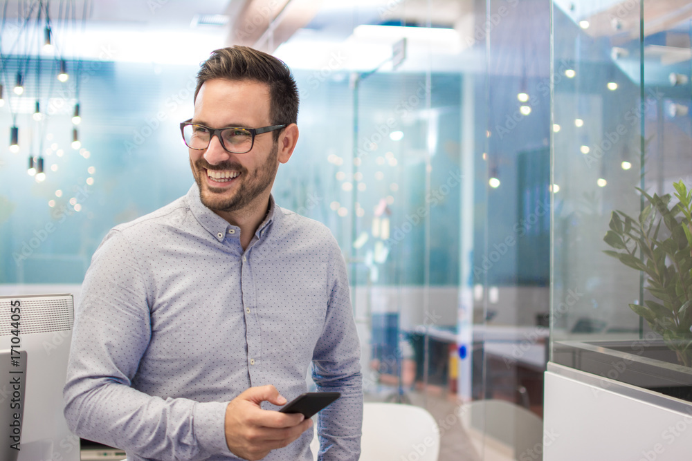 Fototapeta Portrait of cheerful businessman with mobile phone standing in modern office.