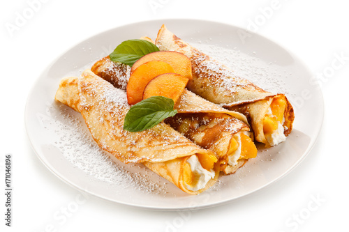 Crepes with peaches and cream on white background