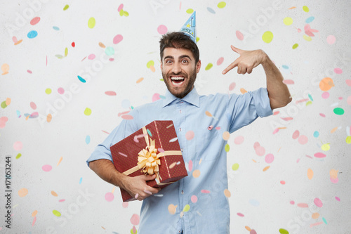 Ecstatic Overjoyed Young Caucasian Man With Holiday Cap On Head Holding Large Box In Wrapping Paper