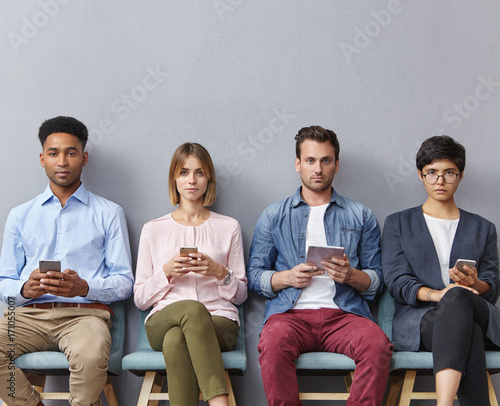 Diverse students sitting on chairs, using modern gadgets