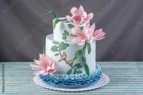 Zdjęcie XXL Piękny ślub w domu trzypoziomowy tort ozdobiony różowymi kwiatami i gałęziami z zielonymi liśćmi w stylu rustykalnym.